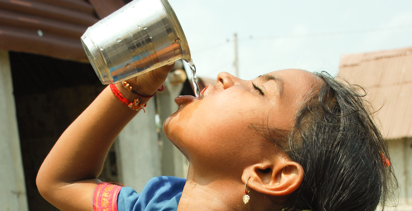 girl drinking clean water in india