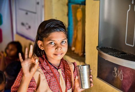 girl-in-self-sustaining-community-in-india-drinking-clean-source-water